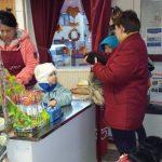 Egy óvodás kislány van a pénztárban, segít a bátyjának és látássérült édesanyjának a fizetésnél.