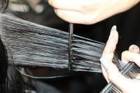 Hajvágás közelről: A fodrász fogja a hajat, megfeszíti és ollóval elvágja.