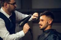A fodrász egy férfi haját szárítja.