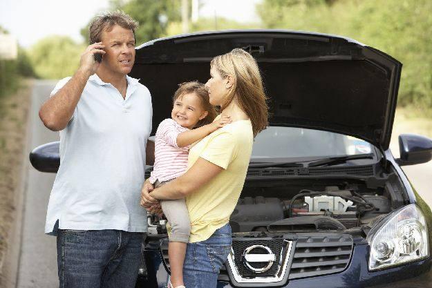 Család autója utazás közbenlerobban. A férj telefonon kér segítséget, az asszony szomorúan vár, kezében egy vidám kisgyerek.
