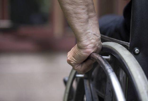 Kerekesszéket hajtó kéz. A képen csak a kerék hajtórúdja és egy kéz látszik.